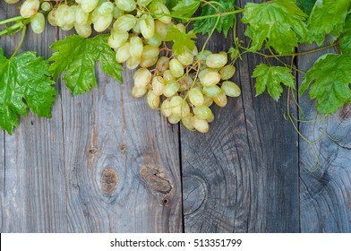 Bunch of grapes with green leaves on the gray wooden old background, top view