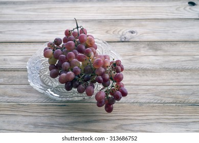 Bunch of grapes on a glass tray on wooden table