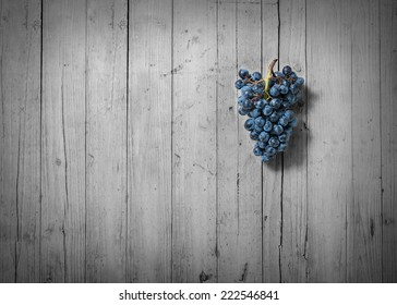 bunch of grapes on old wood and desaturated