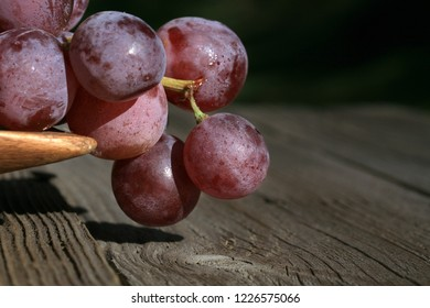 Bunch of grapes on a wooden table an old, country house. An element of outdoor decoration on the occasion of a harvest festival at the end of summer.