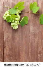 Bunch of grapes and vine on wooden table background with copy space