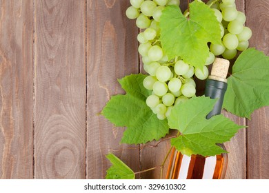 Bunch of grapes and white wine bottle on wooden table background with copy space