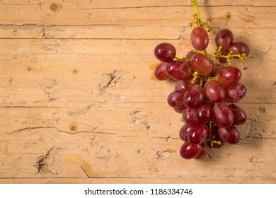 Bunch of grapes without seeds isolated on old wooden background, with space to place your logo