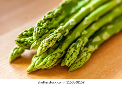 Bunch of green asparagus on a wooden board. Close-up with blured background.