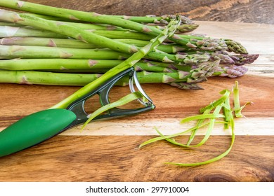 Bunch of green asparagus with peeler on wooden background