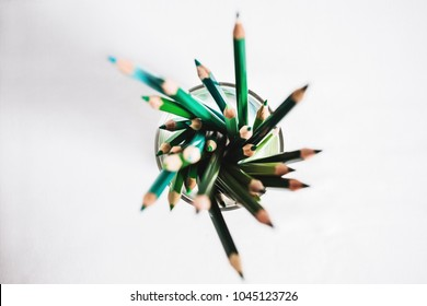 Bunch of green coloured pencils in a glass. Different shades of green. View from above, copy space.