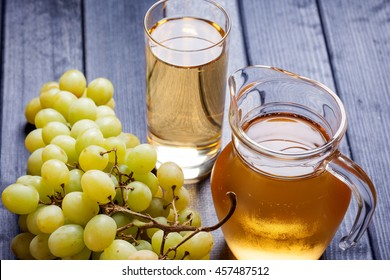 bunch of green grapes and juice in the glass, pitcher