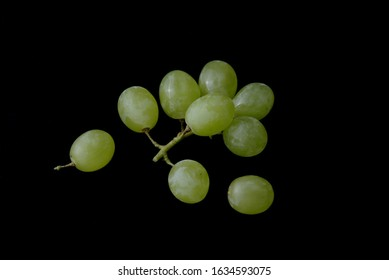Bunch of green grapes on black background