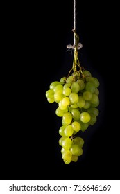 bunch of green grapes on a black background