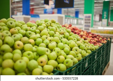 Bunch of green and red apples on boxes in supermarket