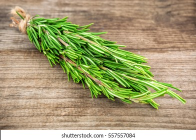 bunch of green scented rosemary on wooden background