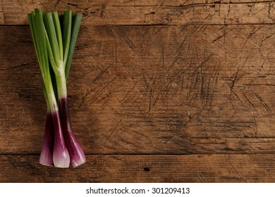 Bunch of green spring onions on rustic wooden background, left side
