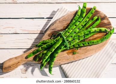 Bunch of grilled green runner beans cooked over a barbecue served on a wooden board on a white picnic table outdoors in summer, overhead view