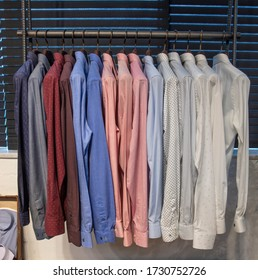 A bunch of hangers with man shirts. Clothes store in the shopping mall. men shirt hanging in the shop for sell.