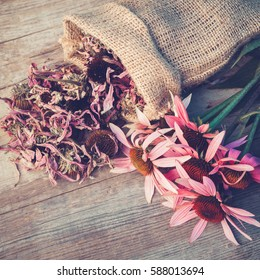 Bunch of healing coneflowers and sack with dried echinacea flowers on wooden board, herbal medicine. Retro toned photo.