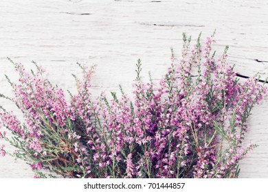 Bunch of heather flower (calluna vulgaris, erica, ling) on shabby wooden table top view. Pastel greeting card in vintage style.