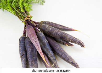 Bunch of heirloom purple carrots, over white and wooden background.