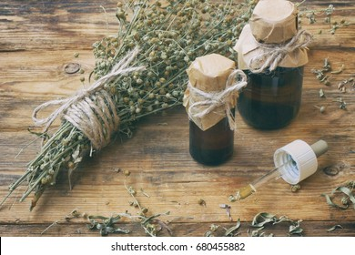 bunch of herb wormwood, jars of oil, on an old wooden table, rustic style, vintage pharmacy