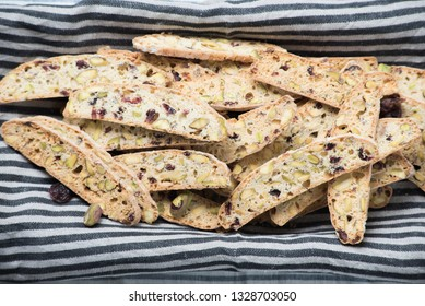 A bunch of homemade pistachio and cranberry biscotti served in a plate lined with a piece of striped cloth.