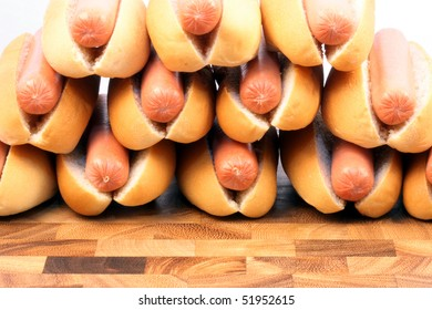 bunch of hot dogs on wood tray, stocked in form of a piramid