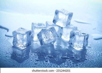 A bunch of ice cubes melting and splashed with water looking fresh and cool on acrylic surface.