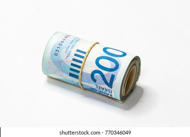 A bunch of Israeli New Shekels (NIS) money notes rolled up and held together with a simple rubber band isolated on a white background.