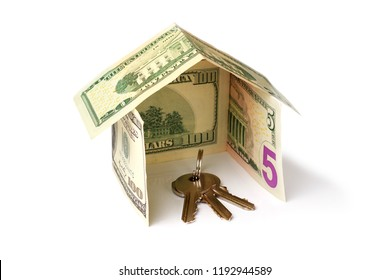 bunch of keys inside a house made from dollar banknotes on white background