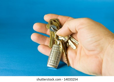 Bunch of keys with a keyring on blue background