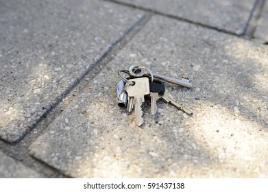 Bunch of keys lying lost on pavement