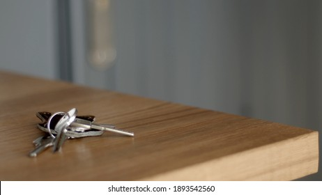 Bunch of keys on a wood light table. Grey wall blur on the background. Minimal close-up high-quality photo.
