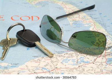 A bunch of keys and sunglasses on a road map