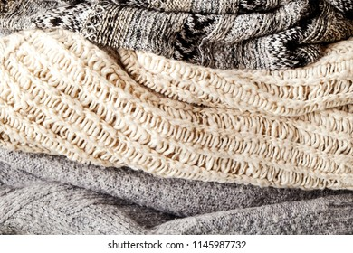 Bunch of knitted warm pastel color sweaters with different knitting patterns laid in messy pile, clearly visible texture. Stylish fall / winter season knitwear clothing. Close up, copy space, top view