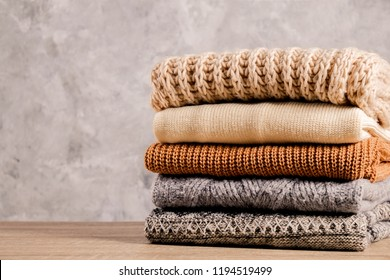 Bunch of knitted warm pastel color sweaters with different knitting patterns folded in stack on brown wooden table, grunged texture wall background. Fall winter season knitwear. Close up, copy space