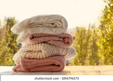 Bunch of knitted warm pastel color sweaters, different knitting patterns folded in stack on white windowsill, window view background. Fall winter season fashionable knitwear. Close up, copy space.