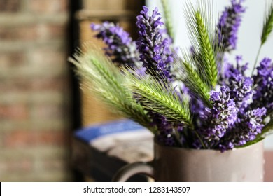 A bunch of lavender and crops in a mug on a coffee table