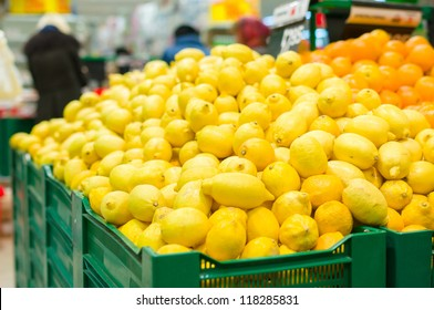 Bunch of lemons and oranges on boxes in supermarket