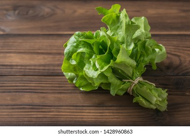 Bunch of lettuce tied with a rope on a wooden table. The concept of healthy eating.