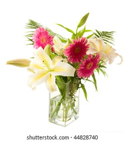 a bunch of lilies and gerberas in the transparent vase on the white background