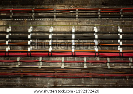 A bunch of live colorful wires at underground. The wires in Tube tunnels provide the communication and power supply functions