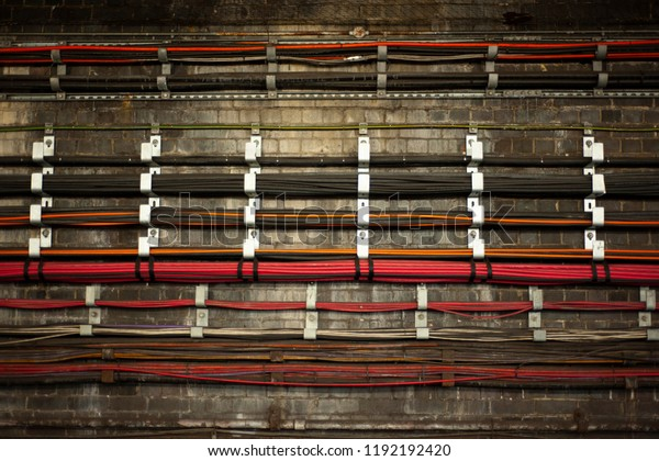 A bunch of live colorful wires at underground. The wires in Tube tunnels provide the communication and power supply functions.