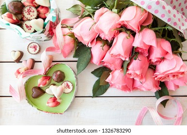 Bunch of lush pink roses and colorful chocolates