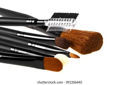 Bunch of make-up brushes lying randomly on white background