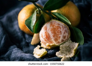 a bunch of mandarin oranges on a dark gray gauze fabric