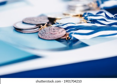 A bunch of marathon finisher's medals lying on certificate. Race running medals from marathon on blue background