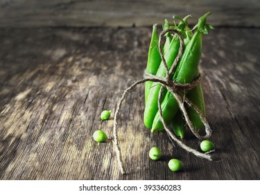 Bunch of mature pods of green peas on the old wooden background. Toned image. Bio healthy food. Selective focus. Copy space background