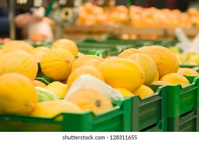 Bunch of melons on boxes in supermarket