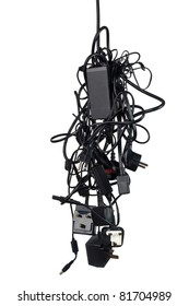 Bunch of messy tangled power cables and adapters isolated on white background