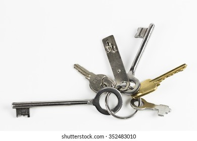 Bunch of metal keys of different shape photographed on white background
