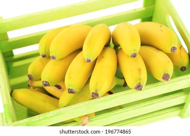 Bunch of mini bananas in wooden box isolated on white
