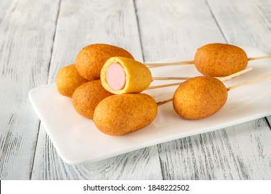 Bunch of mini corn dogs on white serving plate